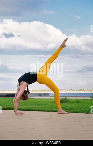 Woman performs yoga in a park on International Yoga Day. Yoga best holistic workout. Mental and physical health. Girl in yoga position. Yoga instructo - Stock Photo