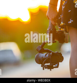 A girl holding a camera mounted on a gimbal. - Stock Photo