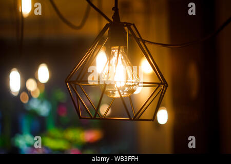 Close up glowing hanging spherical retro vintage edison incandescent bulb in metal lampshade against background of blurred other lamps, selective focu - Stock Photo