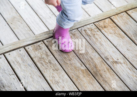 Toddler wearing light blue jeans and pinky purple gumboots walking up a step on wooden deck. The wood is weathered and worn. Gumboots covered in grass - Stock Photo