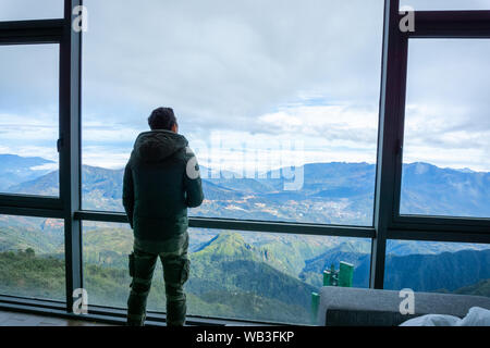 Man travelller overlooking the mountain view from hotel window - Stock Photo