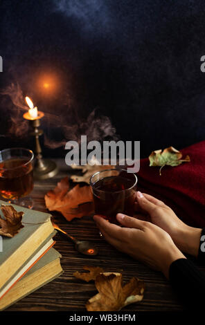 Girl holding a cup of hot tea in her hands. Autumn mood. Cup of tea on a vintage wooden table, candlelight, autumn leaves, books, woolen plaid - Stock Photo