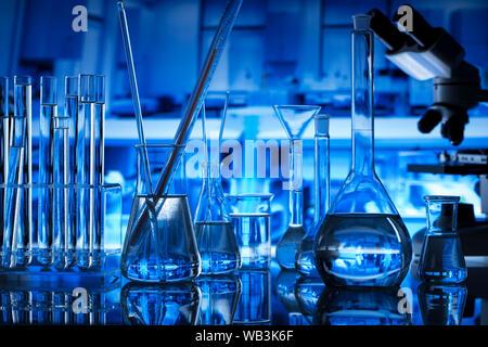 Science laboratory concept background. Microscope and laboratory glassware composition. - Stock Photo