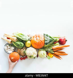 Heap of fresh organic seasonal vegetables and fruits on white background. Woman hand holding little pumpkin. Copy space. Top view. Autumn harvest. Fla - Stock Photo