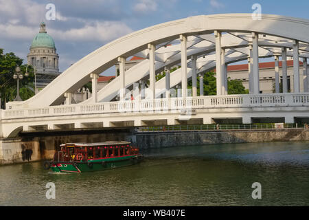 A tour boat on the Singapore River, Singapore, passes under colonial-era Elgin Bridge, the dome of the National Gallery Singapore seen in the b/g - Stock Photo