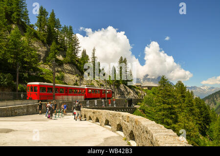 Scenic view with a red train arriving at the rack railway station of Montenvers at the Mer de Glace and tourists in summer, Chamonix, Alps, France - Stock Photo