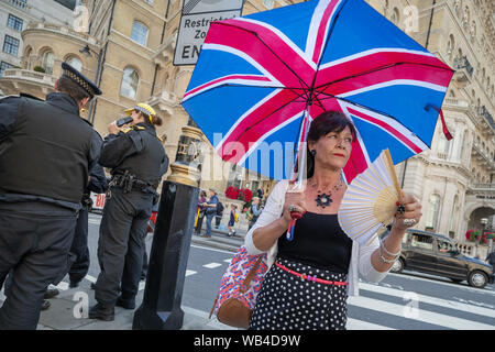 London, UK. 24th August, 2019. UK Weather: 'Free Tommy' nationalist protesters keep cool with fans during the city heatwave whilst waiting to be marched to BBC Broadcasting House in support of the jailed Tommy Robinson, real name Stephen Yaxley-Lennon, who was sentenced last month to nine months in prison after being found guilty in contempt of court. Credit: Guy Corbishley/Alamy Live News - Stock Photo