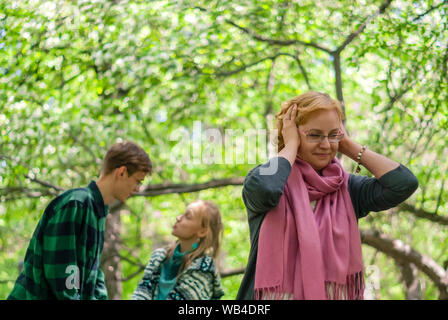 woman clamps her ears, seeking to enjoy the silence, while her two teenage children rustle in the background outdoor Stock Photo