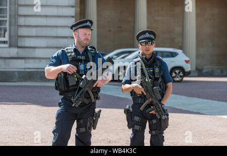 Pair of armed Metropolitan Police officers carrying guns outside Buckingham Palace in City of Westminster, Central London, England, UK. - Stock Photo