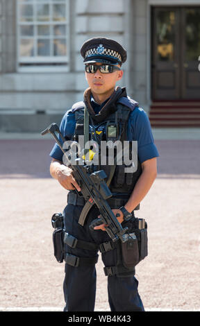Male armed Metropolitan Police officer carrying a gun outside Buckingham Palace in City of Westminster, Central London, England, UK. - Stock Photo
