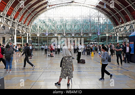 Back view of beautiful young woman in stylish summer skirt fashion standing on concourse at Paddington Station interior London England UK KATHY DEWITT - Stock Photo