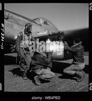 [Edward C. Gleed and two unidentifiedTuskegee airmen, Ramitelli, Italy, March 1945]; Photograph shows Tuskegee airman Edward C. Gleed, Lawrence, KS, Class 42-K, with two unidentified crewmen adjusting an external seventy-five gallon drop takn on the wing of a P-5/D, Creamer's Dream. Ramitelli, Italy, March 1945. (Source: Tuskegee Airmen 332nd Fighter Group pilots.)