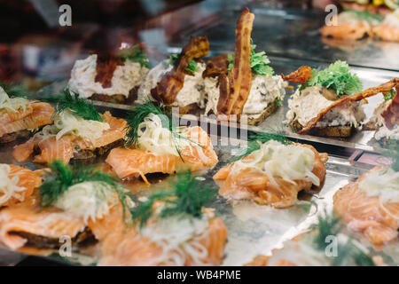 Selection of traditional open-faced Danish sandwiches,  smorrebrod, inside display case at a food market in Copenhagen, Denmark. - Stock Photo