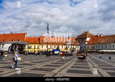 Sibiu, Romania - 2019. Tourist wondering in the panoramic The Big Square (Piata Mare) of Sibiu looking and the City hall. - Stock Photo