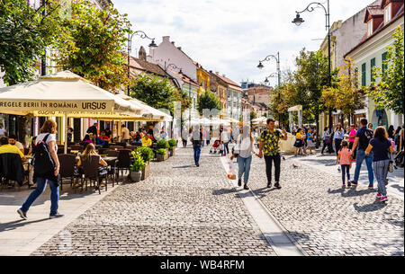 Sibiu, Romania - 2019. People and tourists having lunch and wandering on the streets of Sibiu old town. - Stock Photo