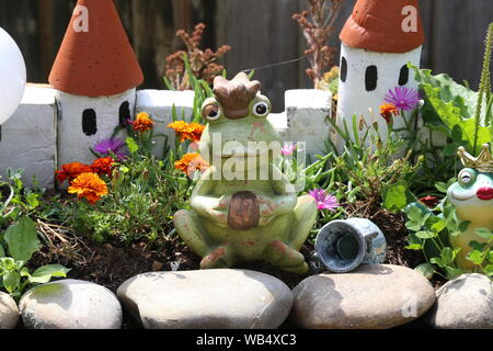 Decorative princess frog by the pond in the garden. - Stock Photo