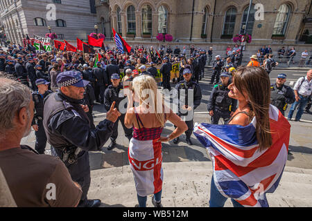 London, UK. 24th August 2019. A woman at the protest at the BBC by Tommy Robinson supporters is warned by the police for offensive language. The protesters claim he is in jail for journalism. He was sentenced to 9 months for 3 offences outside Leeds Crown Court which could have led to the collapse of a grooming gang trial, and has previous convictions for violence, financial and immigration frauds, drug possession and public order offences. Police kept the two groups apart. Robinson supporters were later joined by marchers from Trafalgar Square, and a larger group from Stand Up to Racism came - Stock Photo