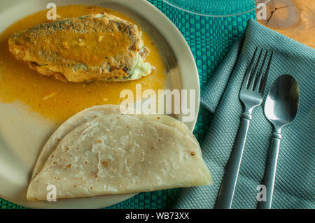 Stuffed Mexican chile poblano with flour tortillas on a dish - Stock Photo