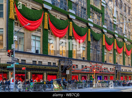 New York, USA - December 07, 2018: Christmas decorations red ribbons, wreaths and lights on the flagship Saks Fifth Avenue store in Manhattan - Stock Photo