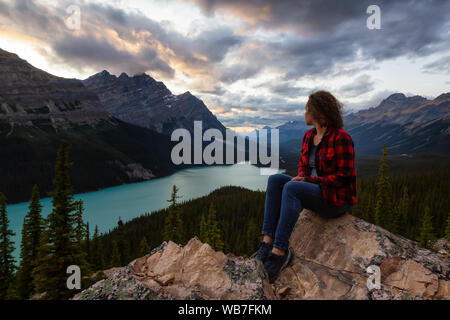 Adventurous girl sitting on the edge of a cliff overlooking the beautiful Canadian Rockies and Peyto Lake during a vibrant summer sunset. Taken in Ban - Stock Photo
