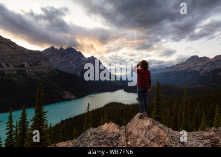 Adventurous girl standing on the edge of a cliff overlooking the beautiful Canadian Rockies and Peyto Lake during a vibrant summer sunset. Taken in Ba - Stock Photo