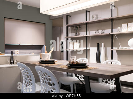 Open plan kitchen and dining room with neutral beige decor, shelving wall unit and a modern table and chairs lit by a large overhead ceiling light - Stock Photo
