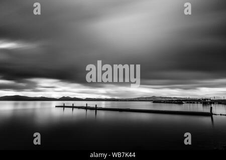 Long exposure view of a pier on a lake, with moving clouds and still water. - Stock Photo