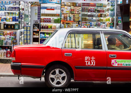 Traditional red taxi cab. Kowloon, Hong Kong, China. - Stock Photo