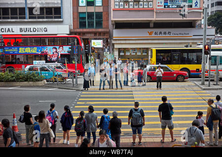 People waiting for green light at pedestrian crossing on Hennessy Road. Causeway Bay, Hong Kong, China. - Stock Photo