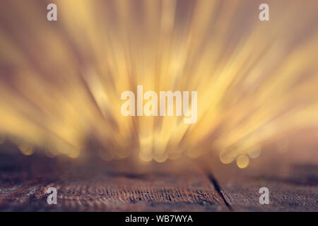 Gold rays of light with bubbles and glitters on wooden background - Stock Photo