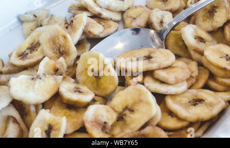 Banana chips in a white breakfast bowl with a spoon - Stock Photo