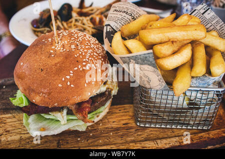 Burger and fries / chips in a basket on a wooden board in a restaurant - Stock Photo