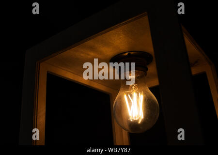 Close-up of warm yellow glowing light bulb encased in a wooden box against a black background - Stock Photo