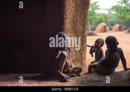 Three children of the Himba tribe in Namibia play in their hut - Stock Photo