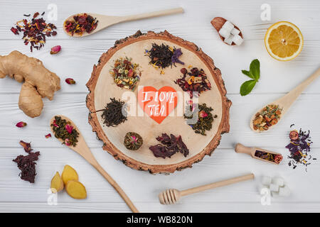 I love tea concept. Different kinds of dry tea on wooden background, flat lay. - Stock Photo
