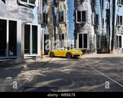 A yellow Porsche car in front of the Gehry building in Duesseldorf - Stock Photo