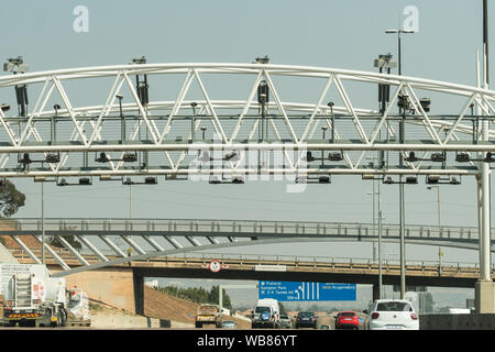 cars and vehicles speed along the N1 highway toll road outside Johannesburg, Gauteng, South Africa underneath an overhead gantry collecting e tolls - Stock Photo