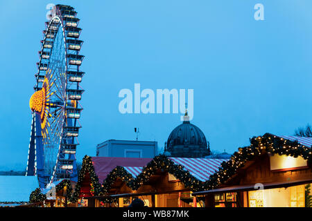 Christmas market with Ferris Wheel in Germany in Europe in winter. German Night street Xmas and holiday fair in European city or town. On Berliner Rat - Stock Photo