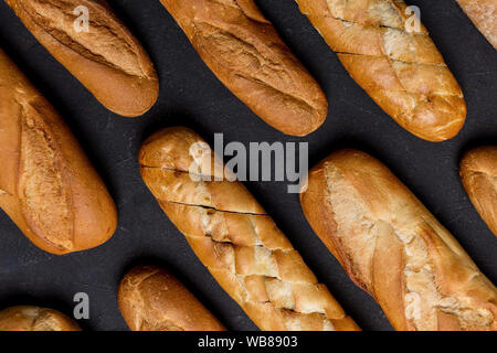 Various bread lie along each other at black background. Concept of harvest food - Stock Photo