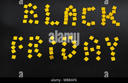 The words BLACK FRIDAY is laid out of golden confetti on black background. Black friday sale concept - Stock Photo