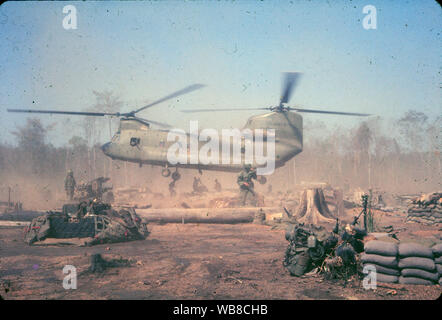 A US Army Chinook helicopter lifts off from a forward military base during the Vietnam War in 1966. - Stock Photo