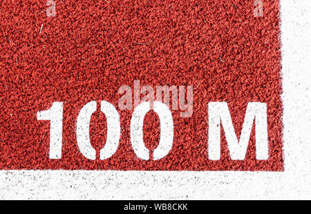 100 M is painted at the start line of the dash on a red track. - Stock Photo