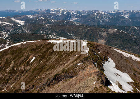 Many layers of mountains one after another. Seen very far away. There are mountains everywhere. In some places there is snow. - Stock Photo