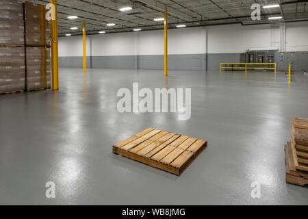 Empty Pallet In Large Warehouse, USA - Stock Photo