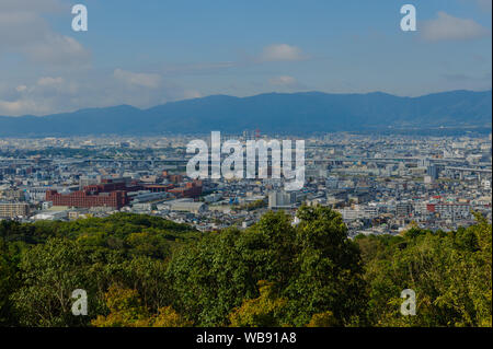 View above Kyotos rooftops captured from the hill of Fushimi Inari-Taisha during the morning hours, Japan November 2018 - Stock Photo