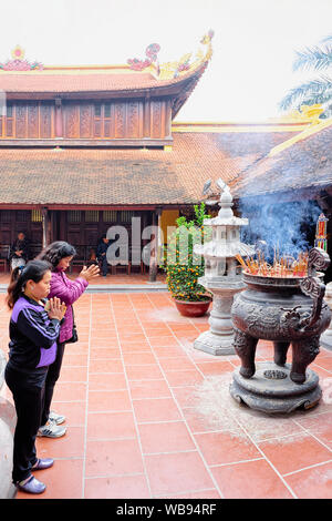 Hanoi, Vietnam - February 22, 2016: Women praying at burning incense bowl at Tran Quoc pagoda on West Lake in Hanoi, capital of Vietnam in Southeast Asia. Traditional church architecture - Stock Photo