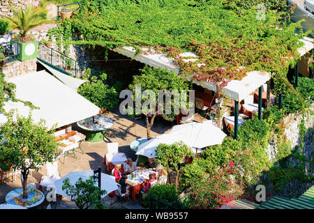 Positano, Italy - September 30, 2017: People at terraced street restaurant in Positano town of Amalfi Coast at Tyrrhenian Sea in Italy in summer. Tables at cafe with view near Sorrento - Stock Photo