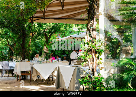 Positano, Italy - September 30, 2017: People at terraced street restaurant at Positano town of Amalfi Coast at Tyrrhenian Sea in Italy in summer. Tables at cafe with view near Sorrento - Stock Photo