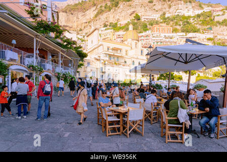 Positano, Italy - September 30, 2017: People at terraced street restaurant in Positano town on Amalfi Coast at Tyrrhenian Sea in Italy in summer. Tables at cafe with view near Sorrento - Stock Photo