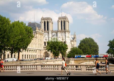 Paris, France - July 7, 2018: View of Notre Dame de Paris with Pont Neuf with walking tourists and Parisians - Stock Photo